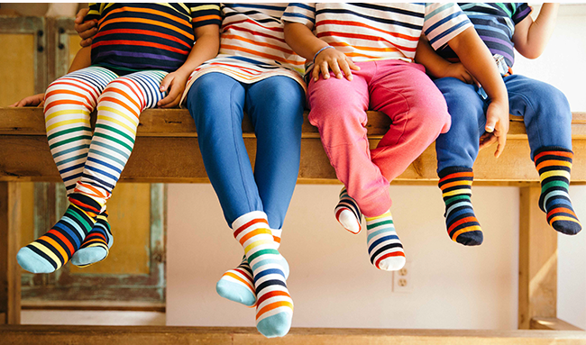 photo of kids sitting on a table dangling their legs, wearing rainbow socks