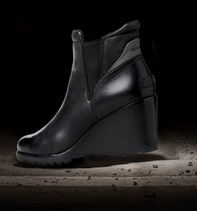 A profile view of a black After Hours Chelsea boot against a black background.