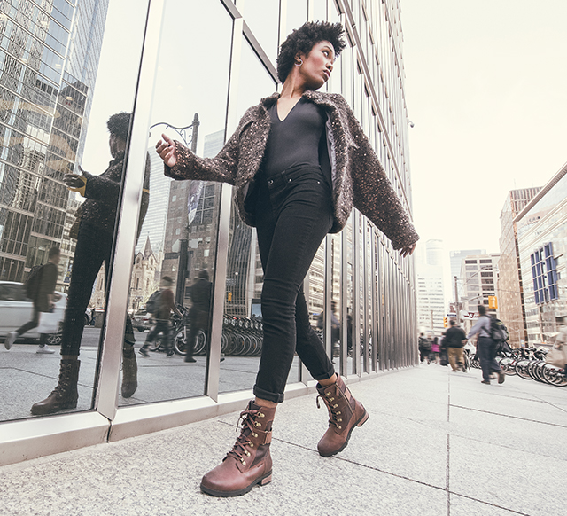 Woman walking through the city wearing a pair of  Emelie Conquest boots