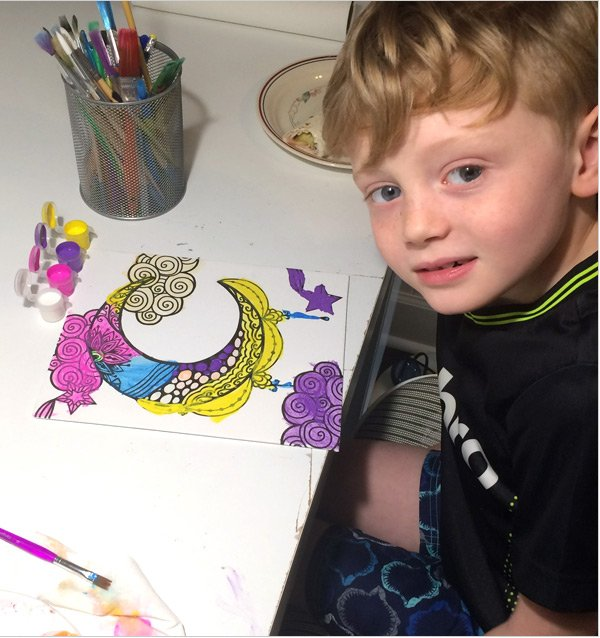 Child creating a colorful black light painting.