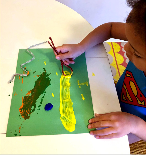 Little girl creating an abstract painting with unique objects.