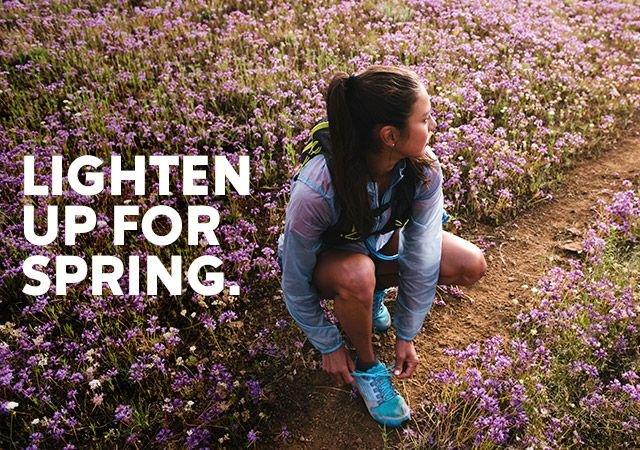 A woman tying her shoe in a field of flowers.