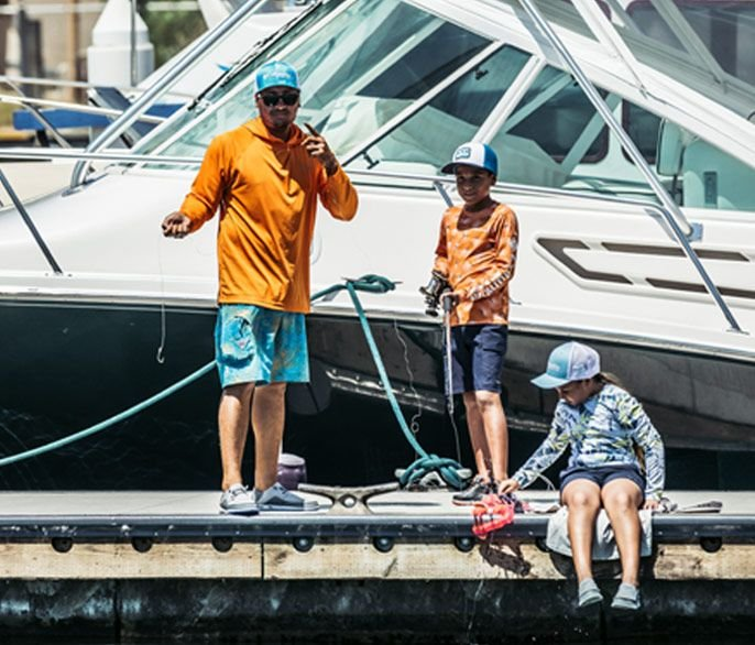 A man and his kids getting ready to fish.