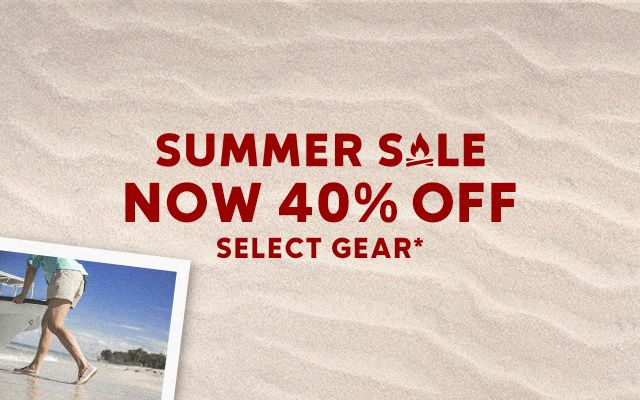 A photo of a man pulling a boat onshore on top of a sandy background. Summer Sale now 40 percent off select gear.