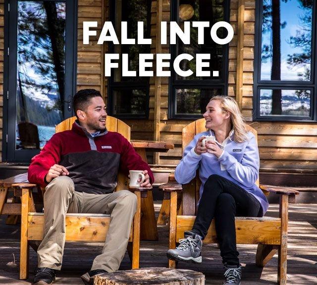 A couple in fleece jackets sitting on a cabin porch enjoying warm drinks. Fall into Fleece.