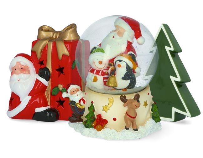 Conjunto de figuritas decorativas navideñas con un santa pequeño con un regalo rojo grande, una esfera navideña con un santa adentro y un arbolito de navidad. Pulsa aquí para encontrar todo en decoración navideña
