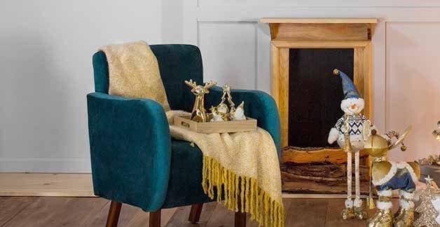 Sillón ocasional tapizado en azul con descansabrazos alto y rodeado de adornos navideños. Pulsa aquí para encontrar más sillones ocasionales