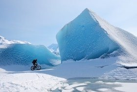A person riding a bike past an iceberg in Alaska