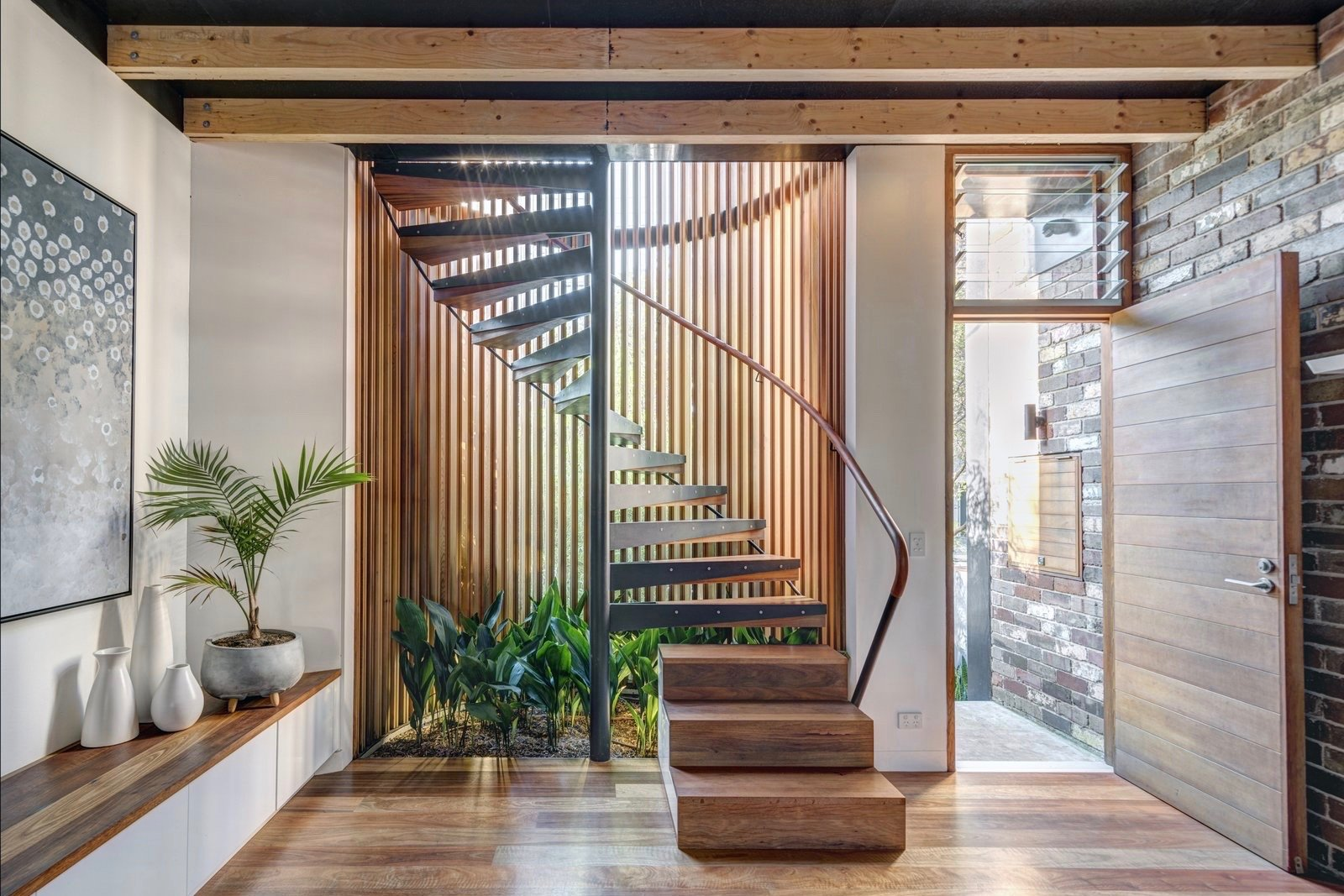 a-cylindrical-glass-staircase-with-western-red-cedar-and-painted-steel-mullions-dominates-the-front-of-the-house-the-stair-treads-along-with-the-floor-are-made-of-recycled-spotted-gum